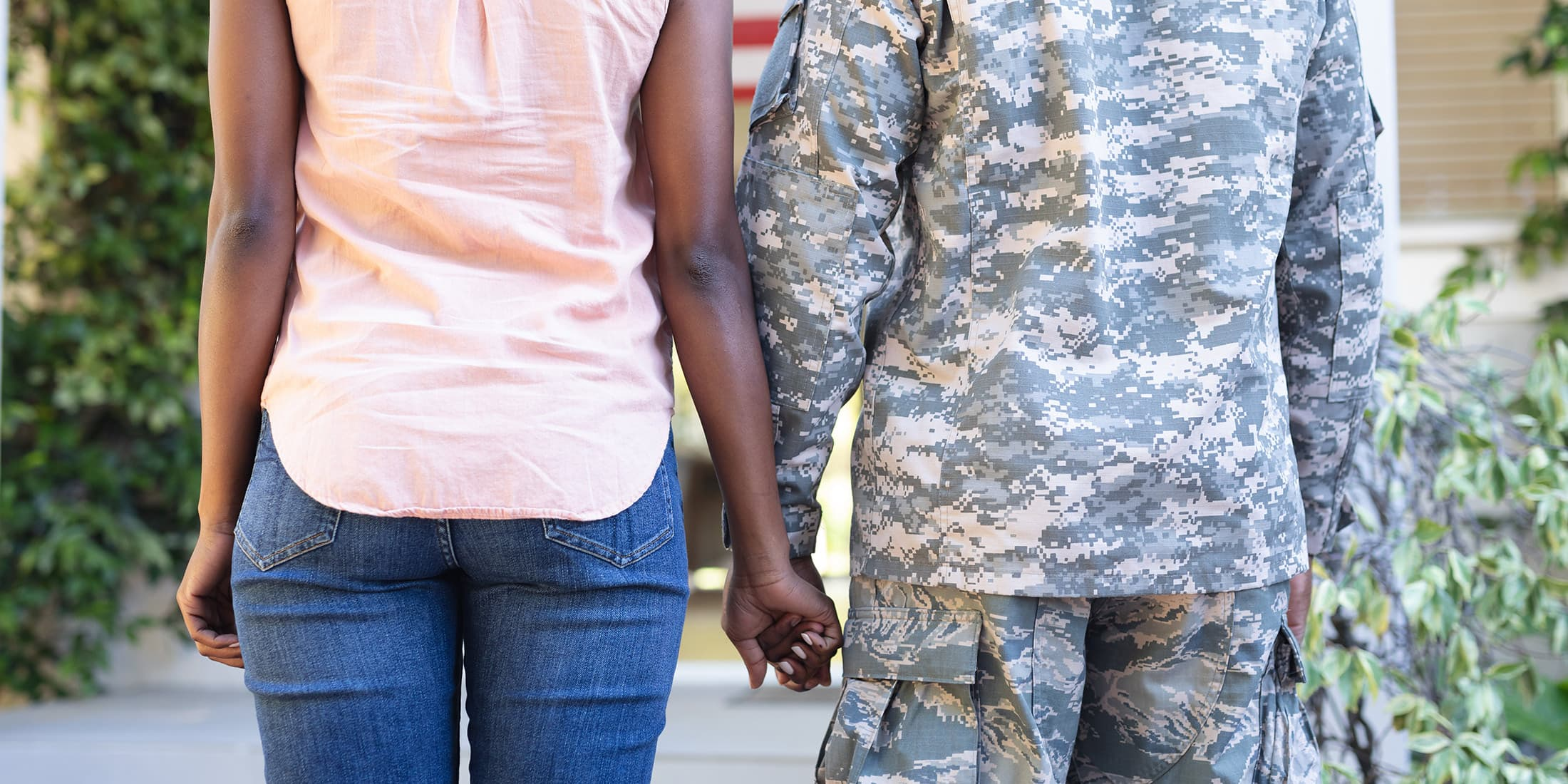 soldier and partner holding hands