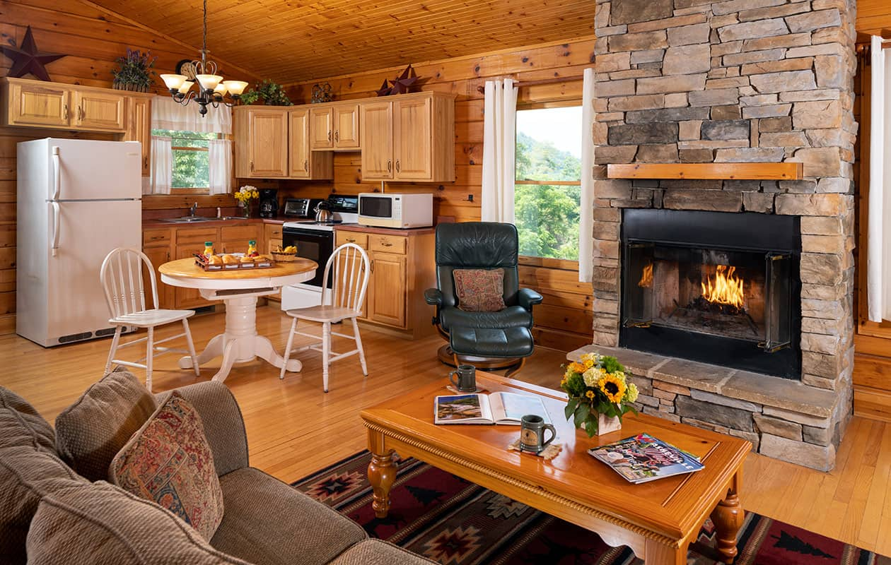 Fully equipped kitchen with living room and fireplace in Cherokee Cabin